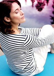 Medelålders kvinna med stängda ögon sitter ner och ser avslappnad ut. Bilden illustrerar hur kroppen förändras och vad some sker runt och efter klimakteriet.