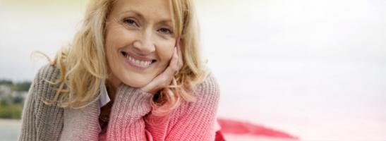 Vänstercentrerad bild på en medelålders kvinna som ler.