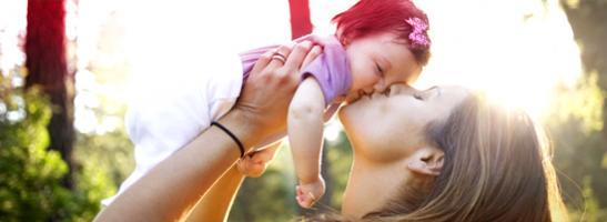 Bild på en kvinna som pussar och håller en bebis.
