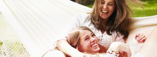 Bild på två leende kvinnor som ligger i en hängmatta. Bilden illustrerar vikten av att vara avslappnad och ha en bra kommunikation.