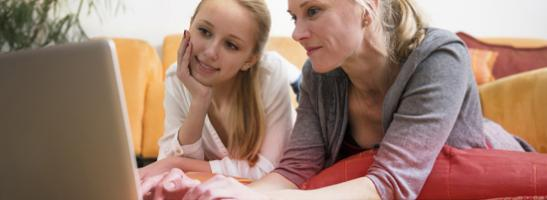Bild på mor och dotter som använder en dator tillsammans. Bilden illustrerar vikten av kommunikation och att hjälpa din dotter att hitta rätt information.