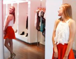 Bild på en flicka som står framför en spegel och provar kläder.