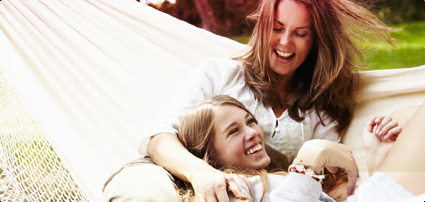 Bild på två leende kvinnor som ligger i en hängmatta