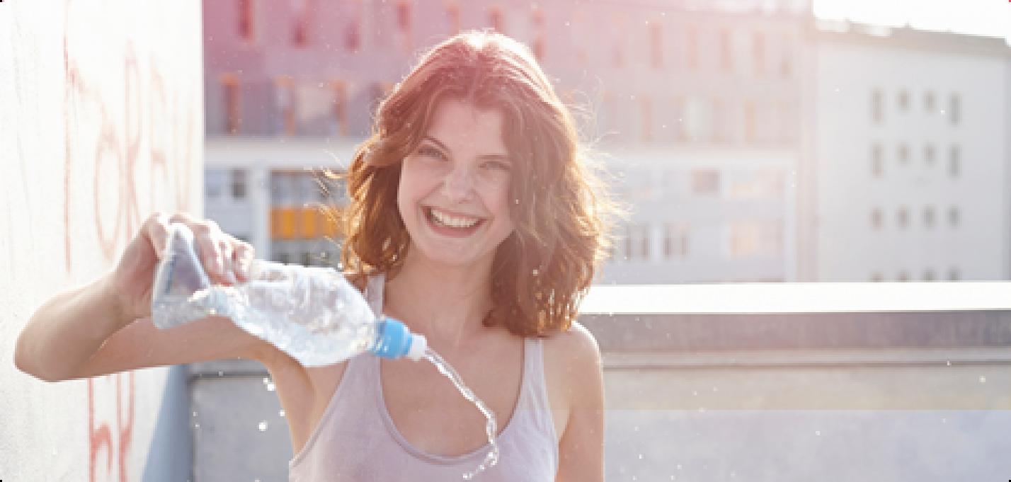 Bild på en ung leende kvinna som håller en vattenflaska i handen och sprutar vatten.