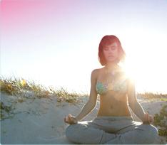Bild på en kvinna som sitter på stranden och mediterar. Bilden illustrerar att det går att koppla av och leva som vanligt även när du har mens.