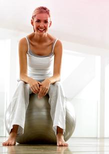 Bild på en kvinna i träningskläder som sitter på en gymboll. Bilden illustrerar att det går bra att motionera och träna även när du hard in mens.