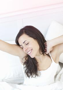 Bild på en ung kvinna som precis har vaknat upp. Bilden illustrerar att du kan sova med en tampong och vakna upp och känna dig fräsch.