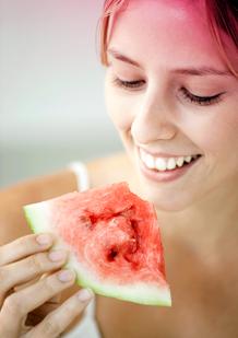 Bild på en ung kvinna som äter vattenmelon. Bilden illustrerar ett av tipsen för att lindra mensvärk - äta frukt eller grönsaker som innehåller mycket vatten.