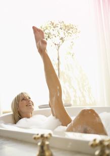 Bild på en kvinna i ett badkar med ett uppsträckt ben. Bilden illustrerar att det går att koppla av och leva som vanligt, även under din mens.