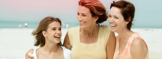 Bild på 3 kvinnor som håller om varandra, en yngre kvinna till vänster och två äldre kvinnor till höger