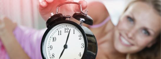 Bild på en väckarklocka med en kvinna i bakgrunden som sträcker sig för att stänga av väckarklockan.