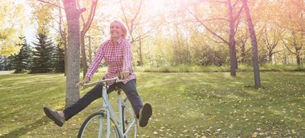 Bild på en kvinna som cyklar. Bilden illustrerar en kvinna som lever och mår bra som vanligt även under menstruationen.