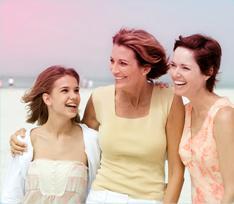 Bild på 3 kvinnor som håller om varandra, en yngre kvinna till vänster och två äldre kvinnor till höger.